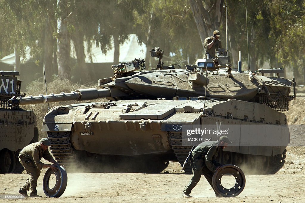 Israeli soldiers prepare their Merkava tank in a training field in the Golan Heights, next to the Israeli-Syrian border, on October 10, 2013. The Israeli army fired on October 9, a Tammuz missile across the Syrian border in response to mortar fire from the Syrian at an Israeli military base in the northern Israeli-annexed Golan Heights leaving two soldiers with light wounds.