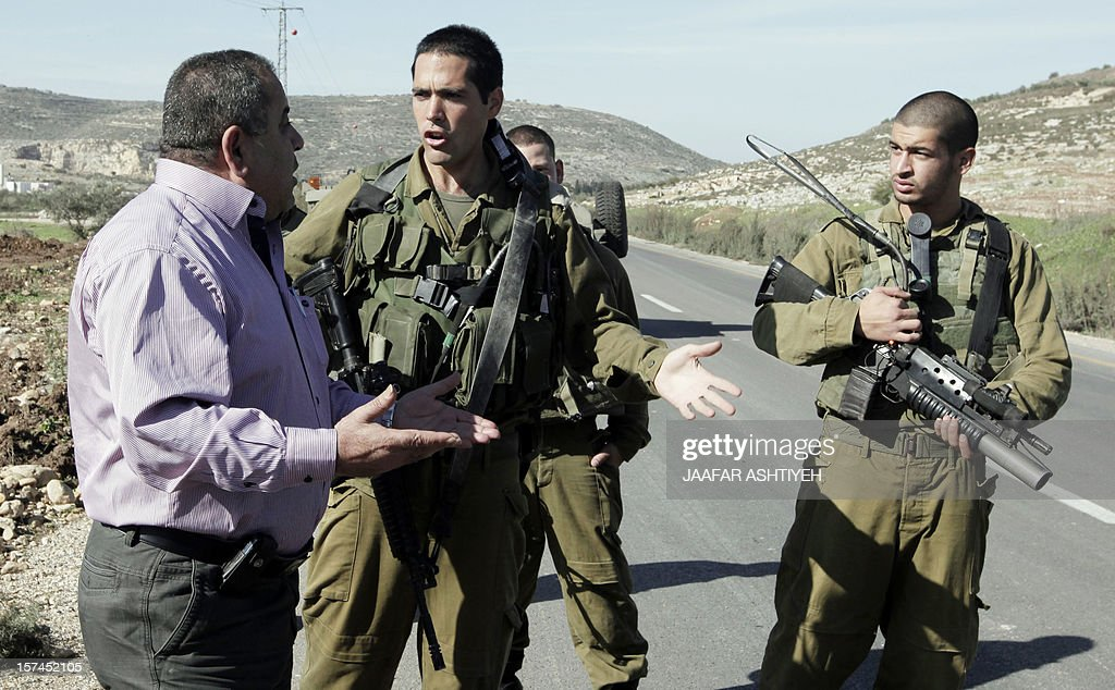 Israeli soldiers prevent a man from approaching the body of his brother, Hatem Shadid, who was shot dead earlier by Israeli forces from the Shin Bet internal security agency after he rammed their car and attacked them with an axe on December 3, 2012 in the West Bank area of Deir Sharaf.