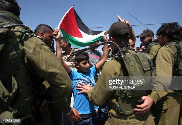 Israeli soldiers push back a young Palestinian demonstrator waving his national flag as he takes part in a protest against Israel's controversial...