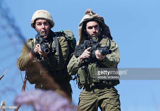 TOPSHOT Israeli soldiers react as they secure the scene of a reported Palestinian shooting attack at a checkpoint near the Beit El settlement close...