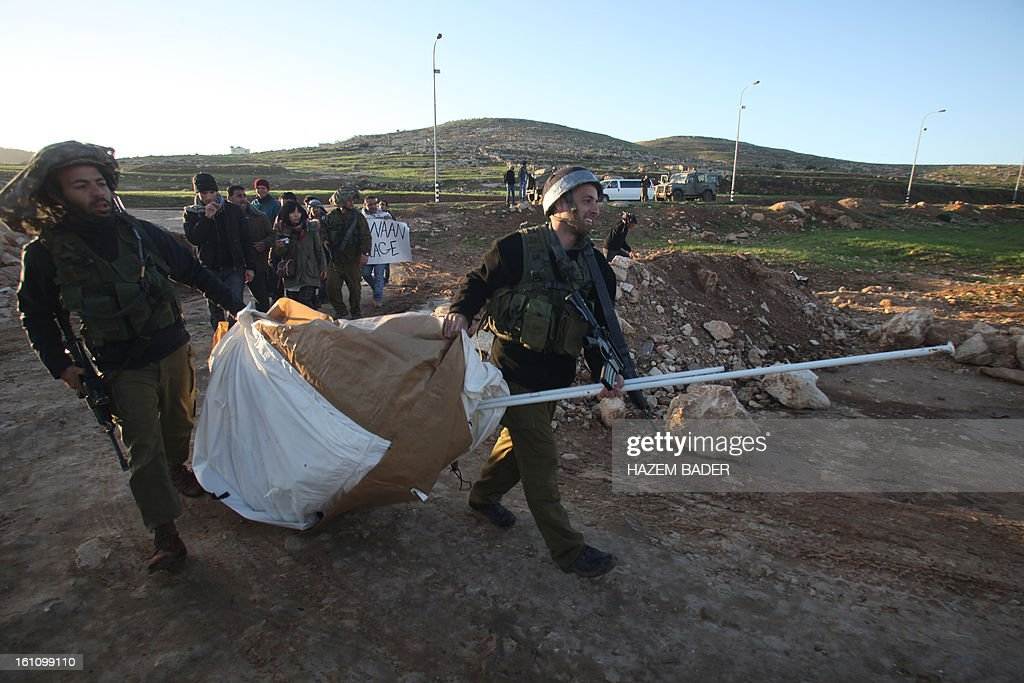 Israeli soldiers remove a tent as Palestinian activists tried to set up a new encampment to protest against settlement building in the Yatta, south of the West Bank city of Hebron on February 9, 2013. Soldiers dismantled tents that were being erected in two different areas near the town of Yatta, and forced activists to leave, the Palestinian witnesses said. BADER