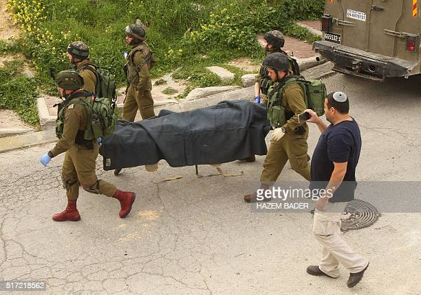 Israeli soldiers remove the body of a Palestinian assailant who was allegedly shot in the head by an Israeli soldier as he lay wounded on the ground...