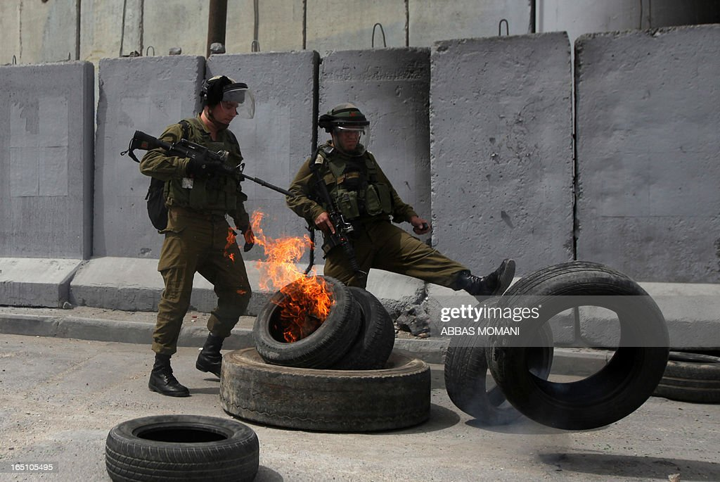 Israeli soldiers remove tyres burning during clashes with Palestinians following a rally commemorating the 37th anniversary of 'Land Day', on March 30, 2013 near the Qalandia checkpoint in the Israeli occupied West Bank. Nearly 200 Palestinians clashed with Israeli forces in Qalandia, who responded with tear gas.