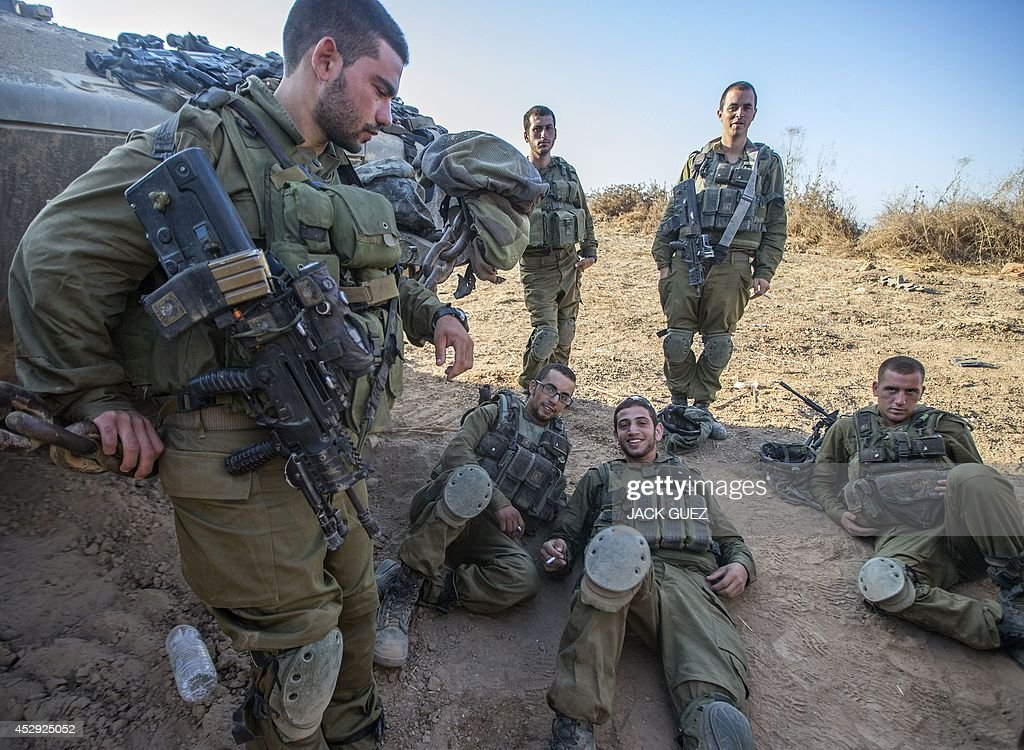 Israeli soldiers rest at an army staging area along Israel's border with the Gaza Strip on July 30, 2014, as they prepare to enter the Gaza Strip. Israel agreed to observe a four-hour lull in Gaza several hours after a deadly strike on a school killed 16, drawing a furious response from a UN refugee agency.