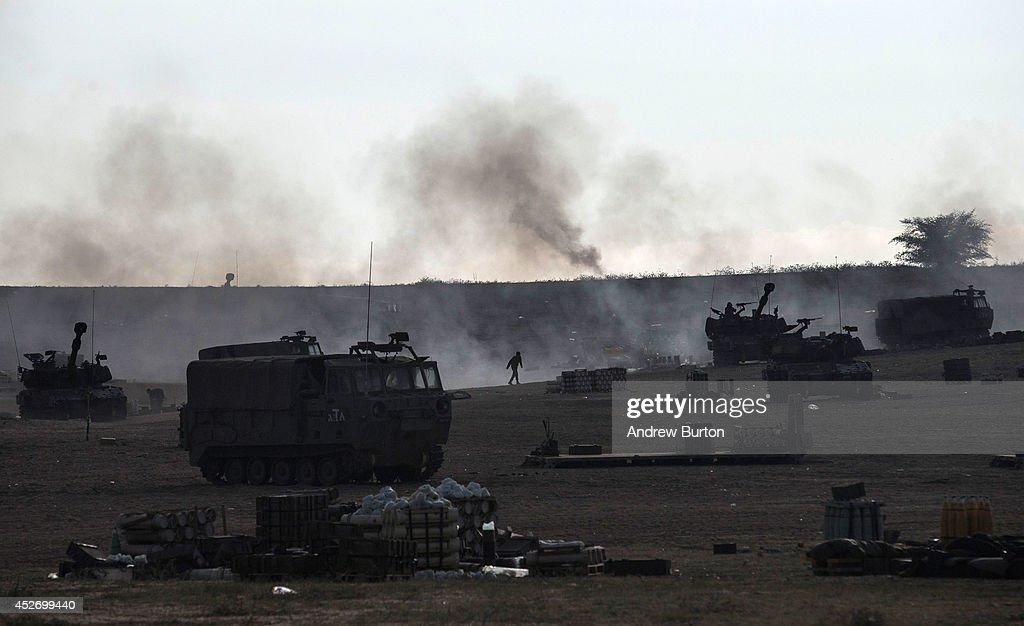 Israeli soldiers run between tanks firing a barrage of artillery shells moments before a 12 hour cease fire goes into effect on the morning of July 26, 2014 near Sderot, Israel. The ceasefire was brokered after nearly three weeks of fighting in which according to recent reports around 40 Israelis and 856 Palestinians have been killed.