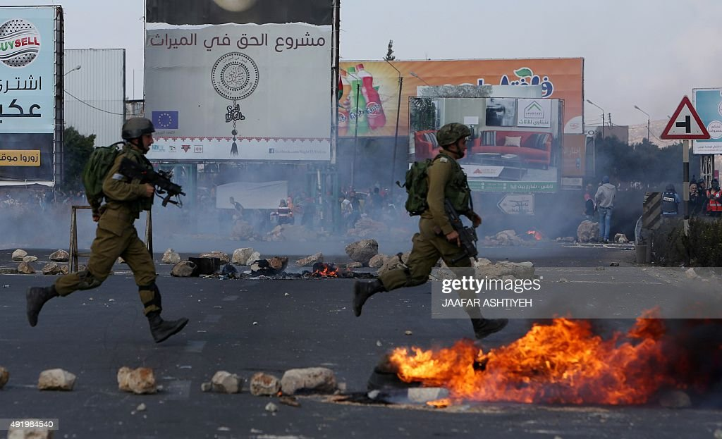 Israeli soldiers run during clashes with Palestinians at the Israelimaned Hawara checkpoint south of the West Bank city of Nablus on October 9 2015 A...