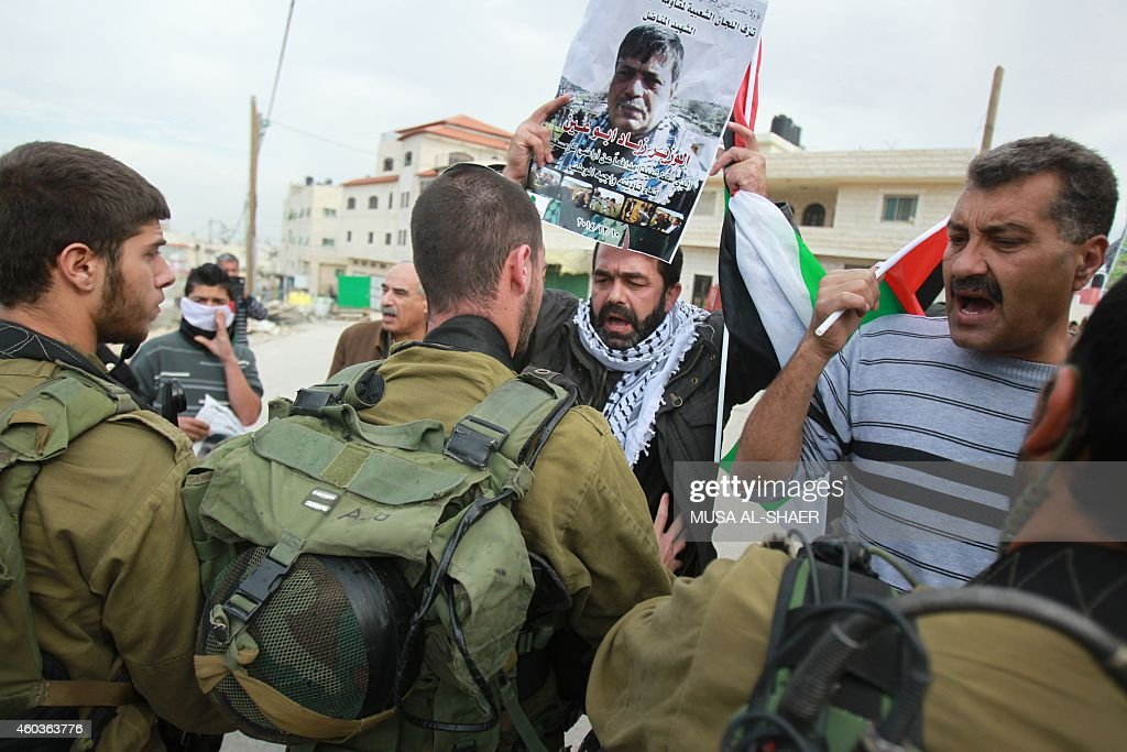 Israeli soldiers scuffle with Palestinian protesters holding a portrait of Ziad Abu Ein a senior Palestinian official who died in a confrontation...