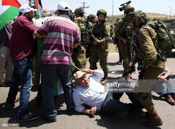 Israeli soldiers scuffle with Palestinian protesters trying to block the main road between the West Bank city of Nablus and the Jewish settlement of...