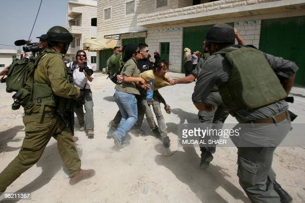Israeli soldiers scuffle with protesters during a demonstration by Palestinians and foreign peace activists against Israel's separation barrier in...