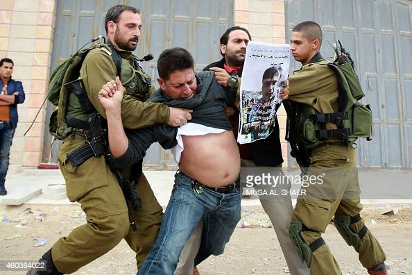Israeli soldiers scuffle with two Palestinian protesters one of them holding a portrait of Ziad Abu Ein a senior Palestinian official who died in a...