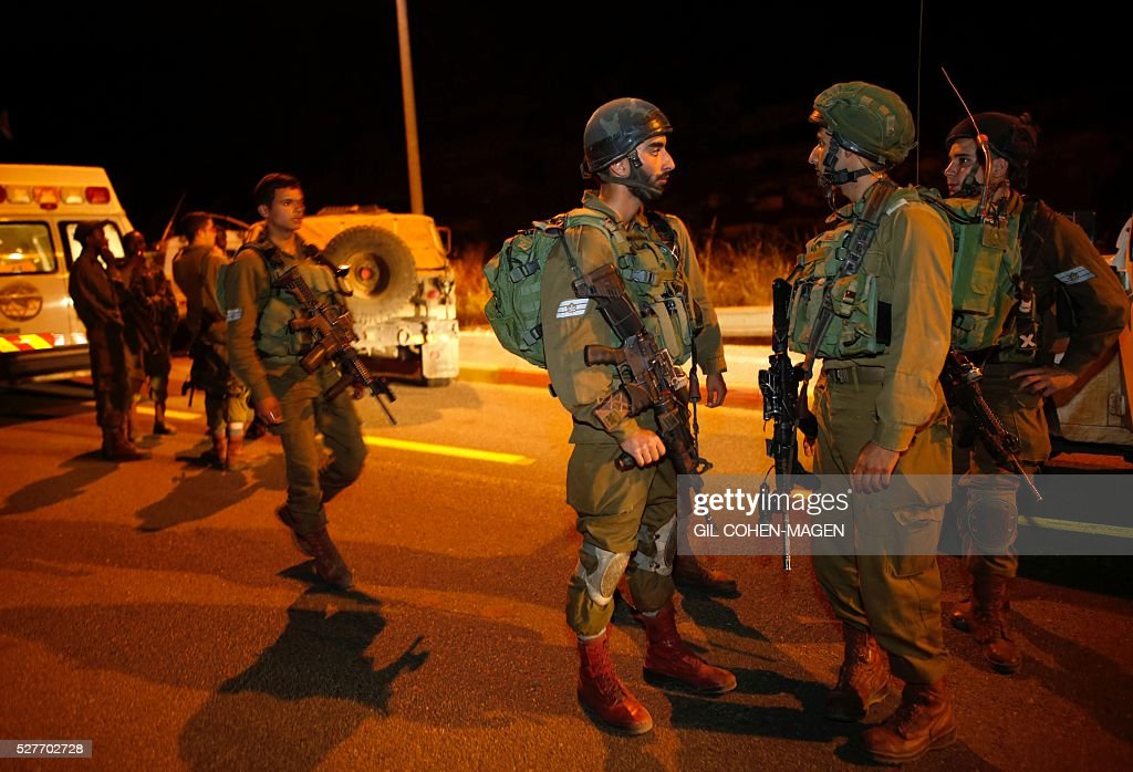 Israeli soldiers secure the area where a car-ramming attack took place near the West Bank settlement of Dolev on May 3, 2016. A Palestinian rammed his car into a group of Israeli soldiers in the occupied West Bank, injuring three before being shot dead, the Israeli army said. MAGEN