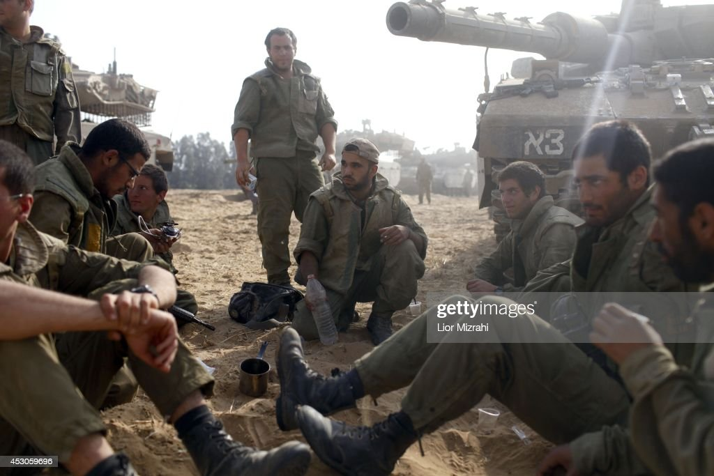 Israeli soldiers sit next to a tank in a deployment area on August 02, 2014 on Israel's border with the Gaza Strip. The Israeli military on Friday cited indications that the officer, Second Lt. Hadar Goldin, 23, was taken captive in Rafah, a city in the Gaza Strip's south. Two other soldiers were killed in the attack, raising the number of Israeli military fatalities to 63. The announcement came not long after a 72-hour humanitarian cease-fire agreed upon by Israel and Hamas collapsed within two hours of being launched.