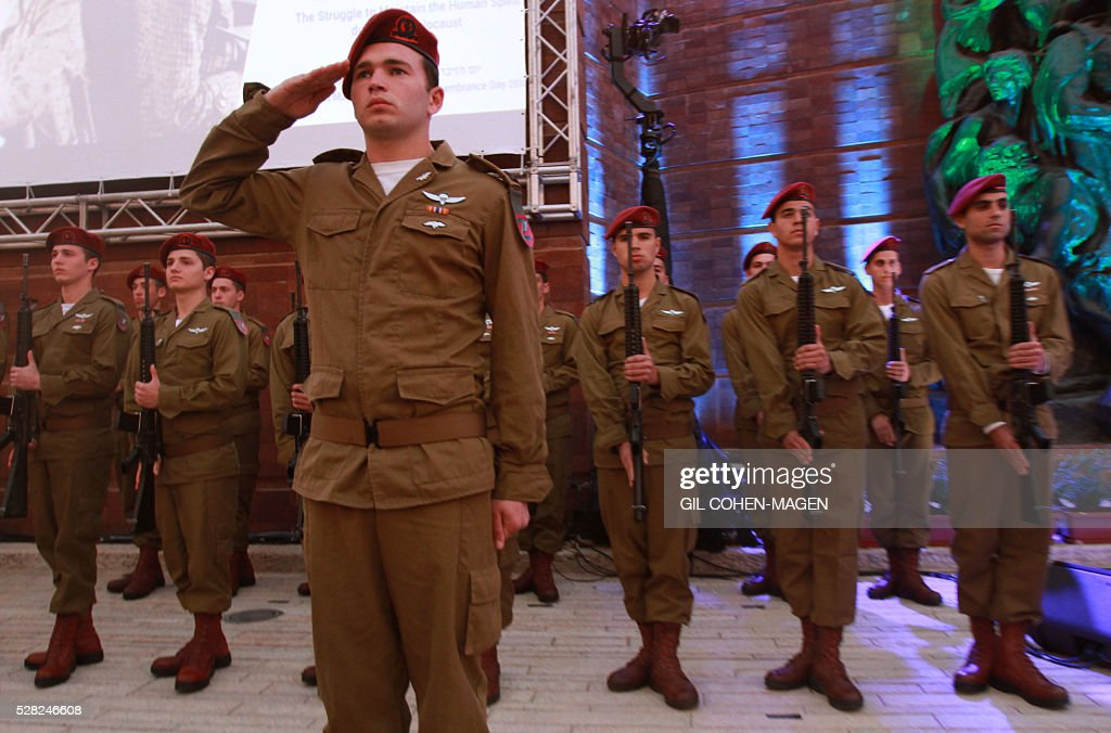Israeli soldiers stand at attention before the start of the ceremony during a ceremony marking the Holocaust Remembrance Day on May 4, 2016 at the Yad Vashem Holocaust memorial in Jerusalem. Holocaust Remembrance Day, commemorating the six million Jews killed by the Nazis during World War II, is an internationally recognized date corresponding to the 27th day of Nisan on the Hebrew calendar and begins this year in the evening of May 4 and ends in the evening of May 5. / AFP / Gil Cohen-Magen
