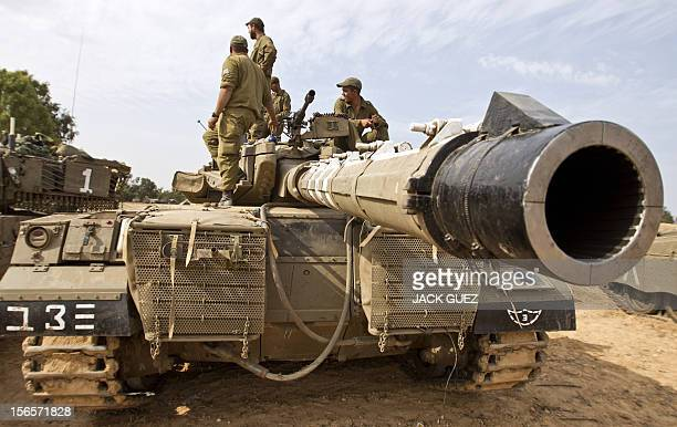 Israeli soldiers stand atop a tank on the Israeli side of the border with the Gaza Strip on November 17 2012 Israeli air strikes destroyed the...