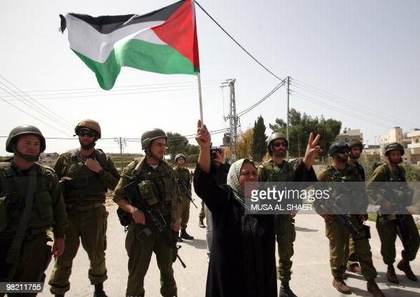 Israeli soldiers stand guard as a Palestinian woman waves her national flag during a demonstration by Palestinians and foreign peace activists...