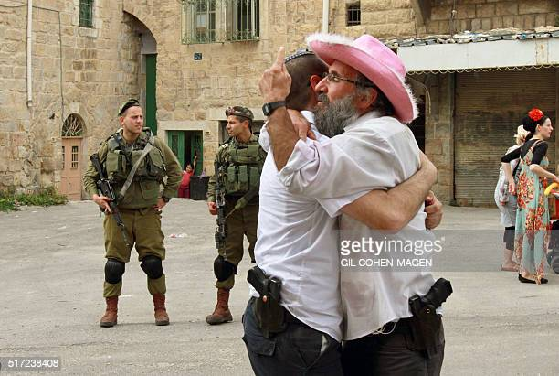 Israeli soldiers stand guard as dressed up Israelis take part in a parade during the festivities of the Jewish feast of Purim on March 24 2016 in the...
