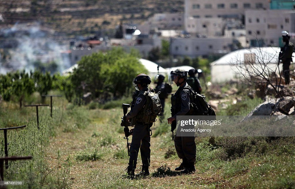 Israeli soldiers stand guard as Israeli bulldozers demolish houses on April 30, 2014 in Al-Aroub refugee camp near Hebron. Israeli bulldozers backed by army troops on Wednesday demolished two houses in the Al-Aroub refugee camp near the West Bank city of Al-Khalil (Hebron).