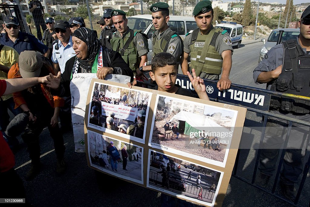 Israeli soldiers stand guard as Palestinian and foreign activists hold signs and pictures outside a Palestinian house occupied by Jewish settlers in the east Jerusalem's Sheikh Jarrah neighborhood during a weekly protest against Israeli settlements and occupation on May 28, 2010.