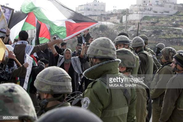 Israeli soldiers stand guard as Palestinian Fatah supporters wave national flags and the yellow flag of Palestinian leader Mahmud Abbas' secular...