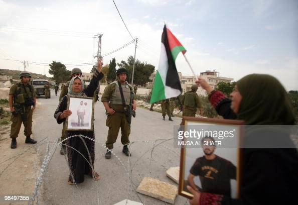 Israeli soldiers stand guard as Palestinian women hold pictures of their jailed relatives during a protest in the village of Maasrah near Bethlehem...