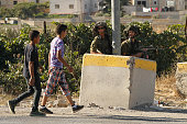 Israeli soldiers stand guard at a checkpoint blocking access to the alFawwar refugee camp south of the West Bank city of Hebron on July 26 before...