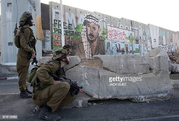 Israeli soldiers stand guard at the Qalandia crossing between the West Bank and Jerusalem during clashes on March 17 2010 with Palestinian protesters...