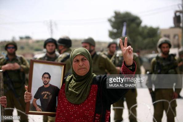 Israeli soldiers stand guard behind barbed wire as a Palestinian woman holds a picture of her jailed relative during a protest in the village of...