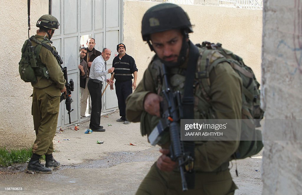 Israeli soldiers stand guard during a raid on the West Bank village of Urif, south of the northern city of Nablus on December 27, 2012. Three Israeli settlers in the West Bank were charged in Beersheva district court with carrying out a 'price-tag' attack against Palestinian property, the justice ministry said.
