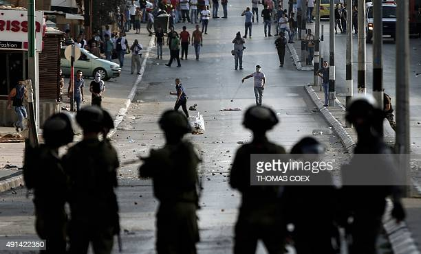 Israeli soldiers stand guard in front of Palestinian stone throwers during clashes in the West Bank town of Bethlehem on October 5 2015 after...