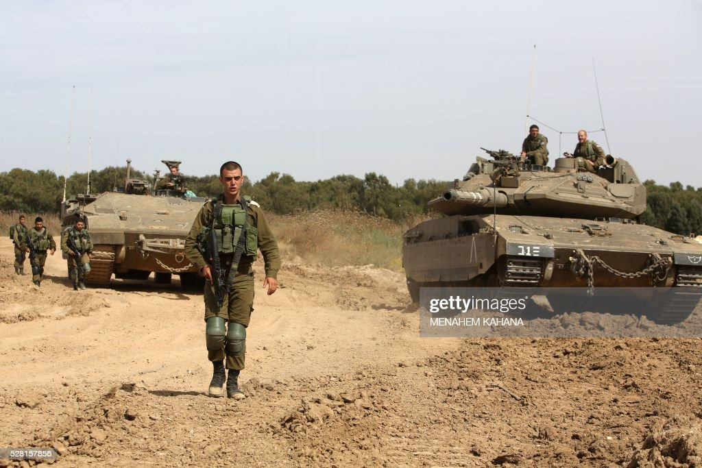 Israeli soldiers stand guard next to a tank and an APC (armoured personal carrier) along the border between Israel and the Gaza Strip near the southern Israeli Kibbutz of Nahal Oz on May 4, 2016. Israeli forces opened fire on positions in the Gaza Strip in response to shellings coming from the Hamas-run Palestinian enclave, said the Israeli army. / AFP / MENAHEM