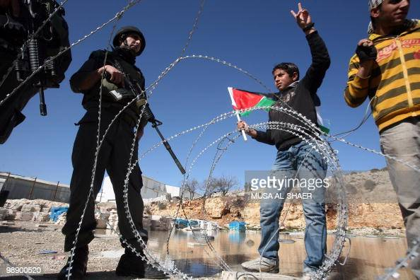 Israeli soldiers stand guard opposite Palestinian protestors flashing the victory sign and waving the Palestinian flag during a demonstration against...