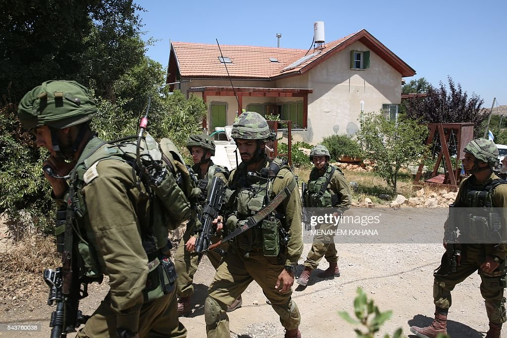 Israeli soldiers stand guard outside a house in the Jewish settlement of Kiryat Arba where a 13-year-old Israeli girl was fatally stabbed in her bedroom on June 30, 2016. A Palestinian attacker stabbed a 13-year-old girl to death at her home in a Jewish settlement in the occupied West Bank before being shot dead by security guards, the Israeli army said. KAHANA