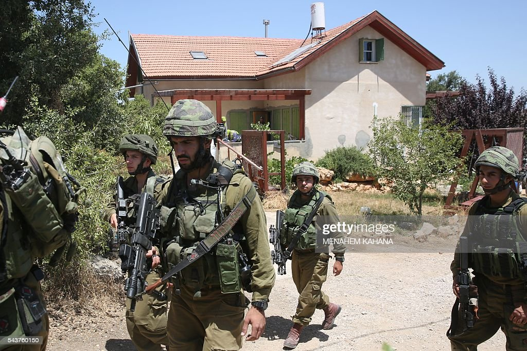 Israeli soldiers stand guard outside a house in the Jewish settlement of Kiryat Arba in the occupied West Bank where a 13-year-old Israeli girl was fatally stabbed in her bedroom on June 30, 2016. A Palestinian attacker stabbed a 13-year-old girl to death at her home in the Jewish settlement outside the city of Hebron before being shot dead by security guards, the Israeli army said. KAHANA