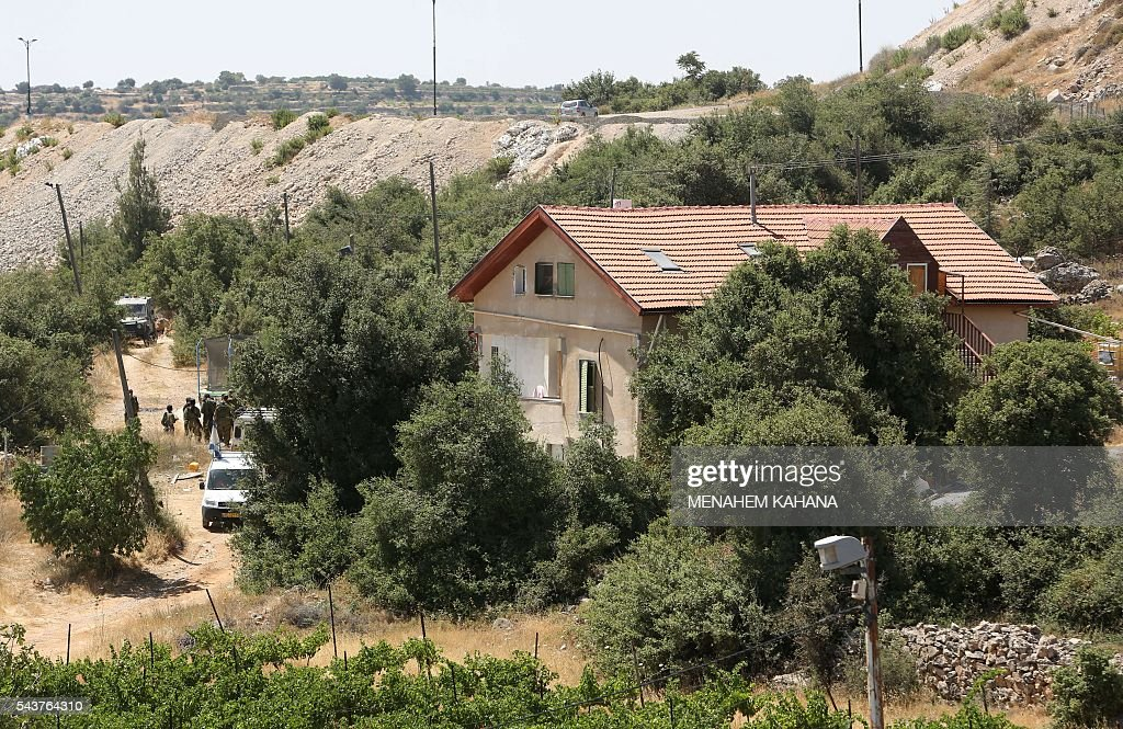 Israeli soldiers (L) stand guard outside a house in the Jewish settlement of Kiryat Arba in the occupied West Bank where a 13-year-old Israeli girl was fatally stabbed in her bedroom on June 30, 2016. A Palestinian attacker stabbed a 13-year-old girl to death at her home in the Jewish settlement outside the city of Hebron before being shot dead by security guards, the Israeli army said. KAHANA