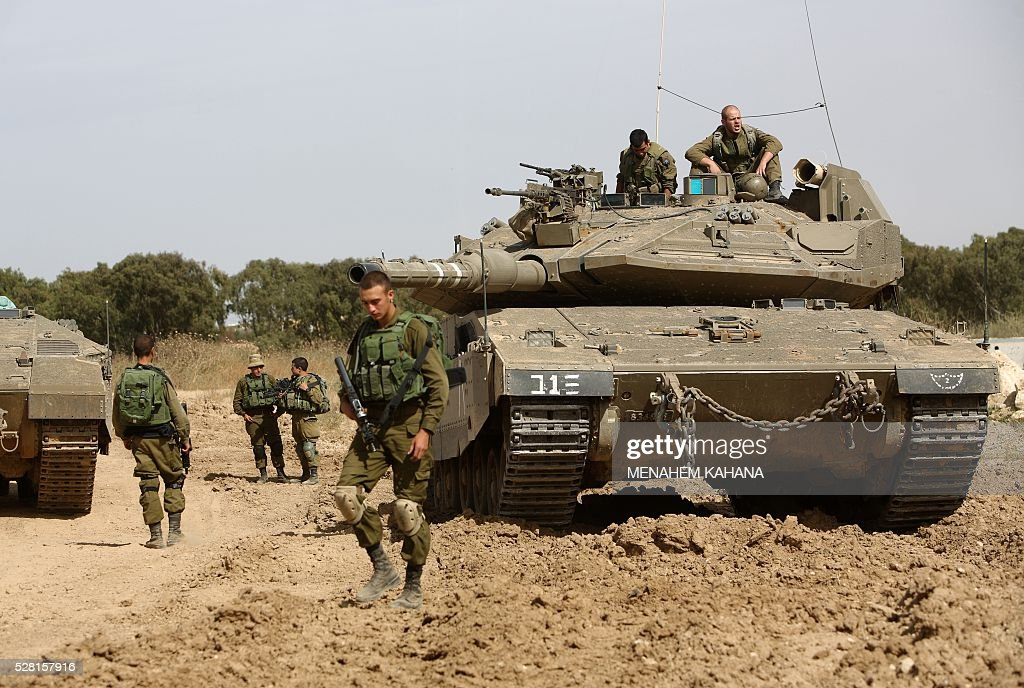 Israeli soldiers stand guard with their tank along the border between Israel and the Gaza Strip near the southern Israeli Kibbutz of Nahal Oz on May 4, 2016. Israeli forces opened fire on positions in the Gaza Strip in response to shellings coming from the Hamas-run Palestinian enclave, said the Israeli army. / AFP / MENAHEM