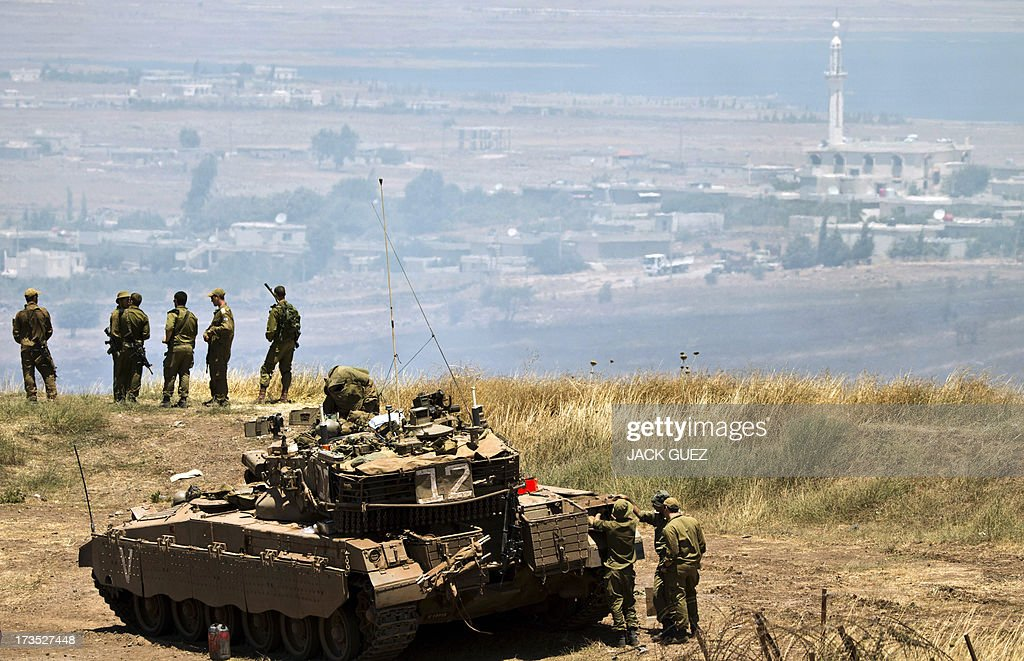 Israeli soldiers stand near a Merkava tank stationed in the Israeli annexed Golan Heights near the Quneitra crossing with Syria (background) on July 16, 2013. Mortar fire from inside war-torn Syria hit the Israeli-occupied Golan Heights causing several wildfires to break out along the ceasefire line, an AFP correspondent reported. The apparently stray rounds struck as Syrian rebels and regime forces battled near Quneitra which lies in no-man's land, the correspondent reported.