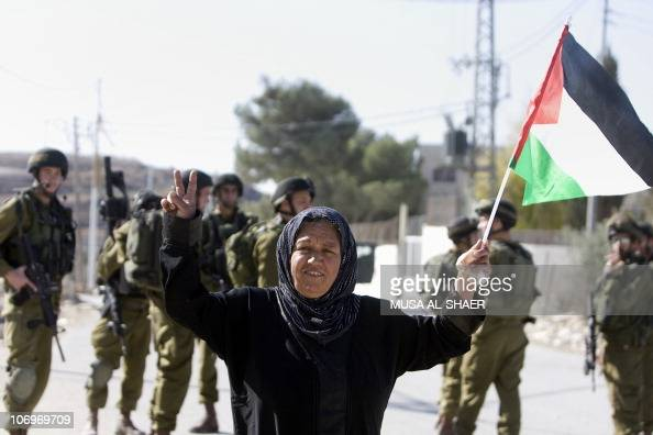 Israeli soldiers stand near a Palestinian women waving her National flag during a protest against Israel's controversial separation barrier in the...