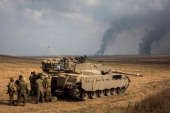 Israeli soldiers stand near their tank while smoke due to airstrikes and shelling rises from Gaza on July 22 2014 near Sderot Israel As operation...