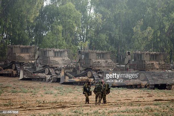 Israeli soldiers stand next Israeli D9 bulldozers in an army deployment area near Israel's border with the Gaza Strip on July 9 2014 The Israeli air...