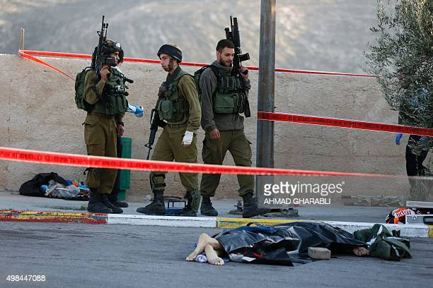 Israeli soldiers stand next to the body of a Palestinian man who was reportedly shot dead by security forces after carrying out a stabbing attack on...