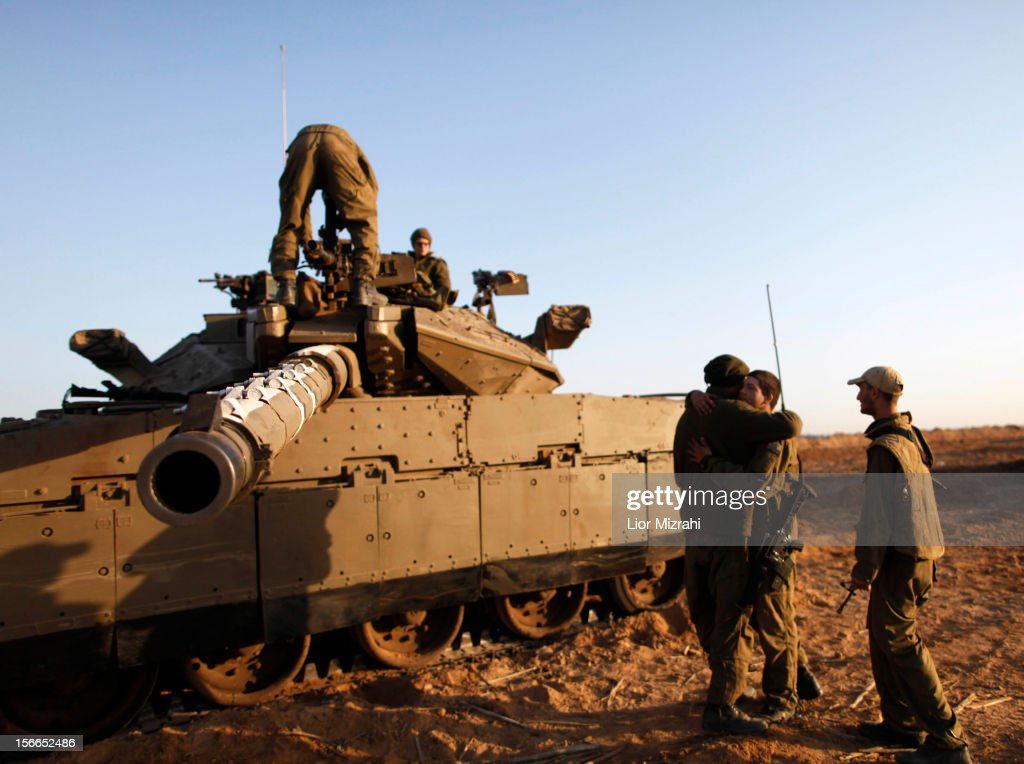 Israeli soldiers stand on and around their tanks in a deployment area on Israel's border with the Gaza Strip on November 18 in Israel Israeli...