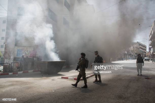 Israeli soldiers stand on guard as they clash with Palestinian youth during the fourth day into the search of three missing teenagers June 16 2014 in...