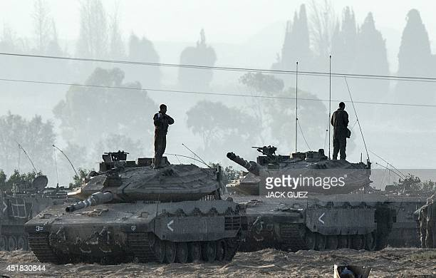 Israeli soldiers stand on Merkava tanks in an army deployment area near Israel's border with the Gaza Strip on July 8 2014 Israeli warplanes pounded...