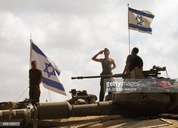 Israeli soldiers stand on top of their Merkava tanks along the border between Israel and the Gaza Strip after they pulled out from the Gaza Strip on...