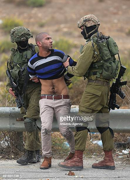 Israeli soldiers take a Palestinian into custody during a protest against preventing Palestinians from entering the AlAqsa Mosque compound on October...