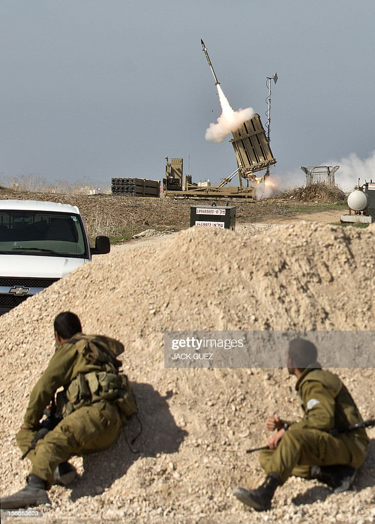 Israeli soldiers take cover as an Israeli missile is launched from the Iron Dome defence missile system, designed to intercept and destroy incoming short-range rockets and artillery shells, in the southern Israeli city of Ashdod, in response to a rocket launched from the nearby Palestinian Gaza Strip on November 18, 2012. Sirens sounded across Tel Aviv for a fourth straight day, AFP correspondents said, as Israeli police confirmed two rockets had been intercepted over the city by the Iron Dome defence system. AFP PHOTO / JACK GUEZ