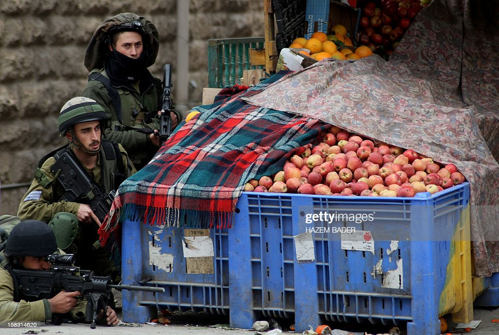 Israeli soldiers take cover behind a fruit stand as they aim at Palestinian stone throwers during clashes following the funeral of Mohamed Ziad Salayma on December 13, 2012, after he was killed the previous day by Israeli forces near his home in the old city of the West Bank town of Hebron. Thousands of Palestinians in Hebron mourned the death of the teenager who was shot after he allegedly threatened Israeli forces with a toy gun.