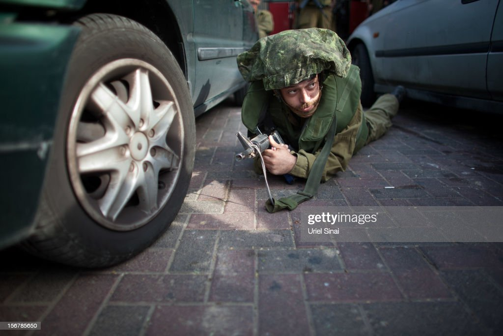 Israeli soldiers take cover during a rocket attack from the Gaza Strip on November 21, 2012 near Israel's border with the Gaza Strip. Despite widespread rumours of a ceasefire militants in the Gaza Strip continue to fire rockets and Israel continues it's bombardment. US Secretary of State Hillary Clinton has arrived in Israel to support and encourage a peace deal being brokered by Egypt.