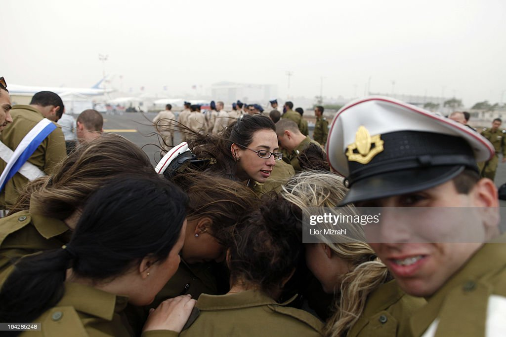 Israeli soldiers take cover from strong winds prior to U.S. President Barak Obama departing from Ben Gurion International Airport on March 22, 2013 in Lod' Israel. Obama concluded his first visit to Israel and West Bank after three-days of meetings with Israeli and Palestinian leaders.