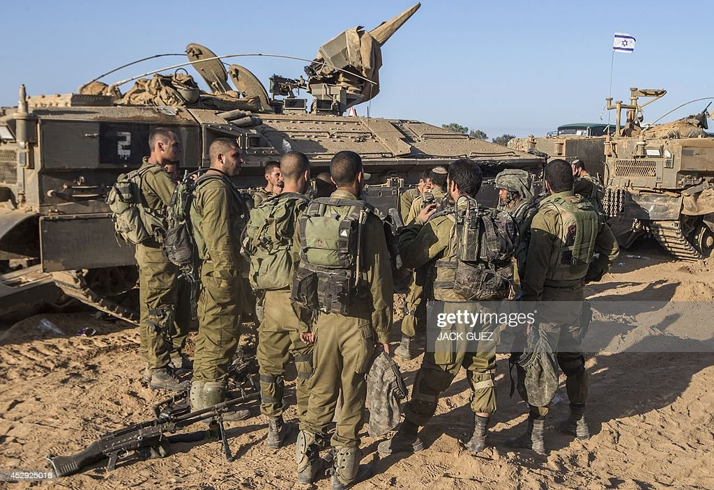 Israeli soldiers take part in a briefing at an army staging area along Israel's border with the Gaza Strip on July 30, 2014, as they prepare to enter the Gaza Strip. Israel agreed to observe a four-hour lull in Gaza several hours after a deadly strike on a school killed 16, drawing a furious response from a UN refugee agency.